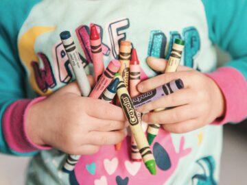 mains d'enfant tenant des crayons de couleurs