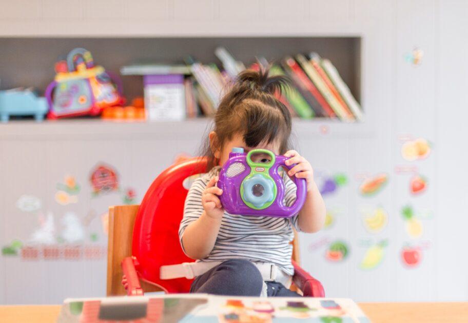 enfant en crèche qui joue avec un appareil photo